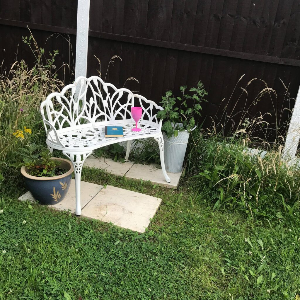 Garden chair with book and gass of cola
